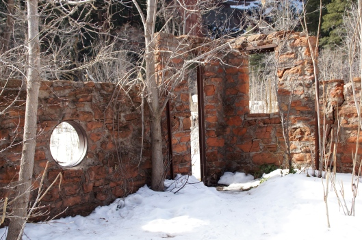 Remains of an abandoned house. Other walls are covered with ivy.